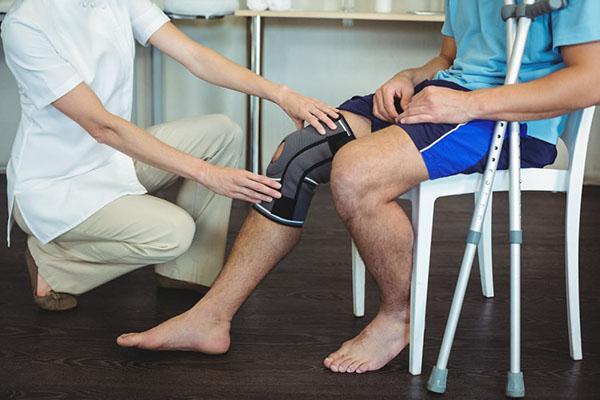 Physiotherapist examining patients knee